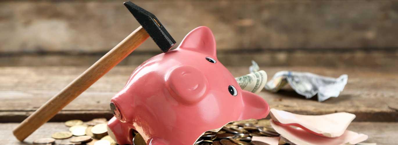 Gehalt eines Ernährungsberaters - Sparschwein wird mit Hammer zerschlagen