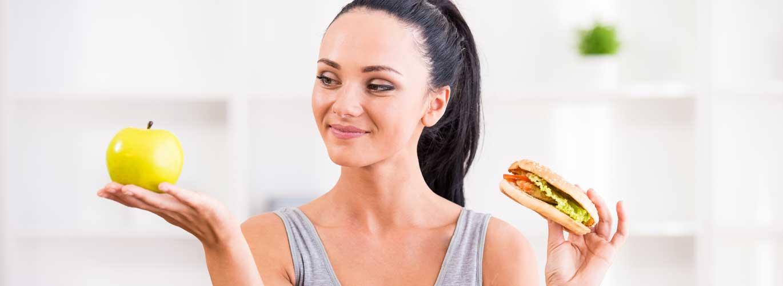 Berufswunsch - Ernährungsberater - Frauhält in einer Hand einen Apfel und in der anderen ein Hamburger