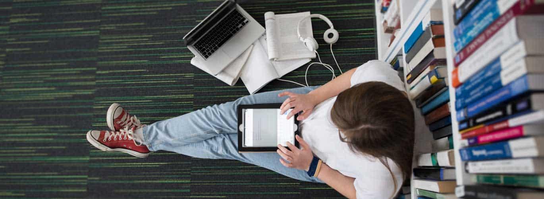 Ernährungsberater Fernstudium - Frau liegt mit Laptop auf Büchereiboden