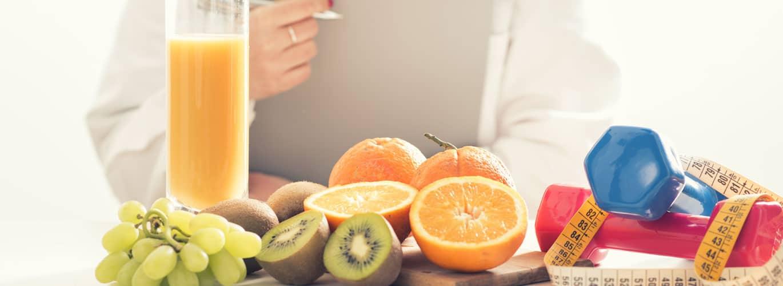 Wie werde ich Ernährungsberater? - Gemüse, Fitnesshanteln und Frau die lernt sind zu sehen