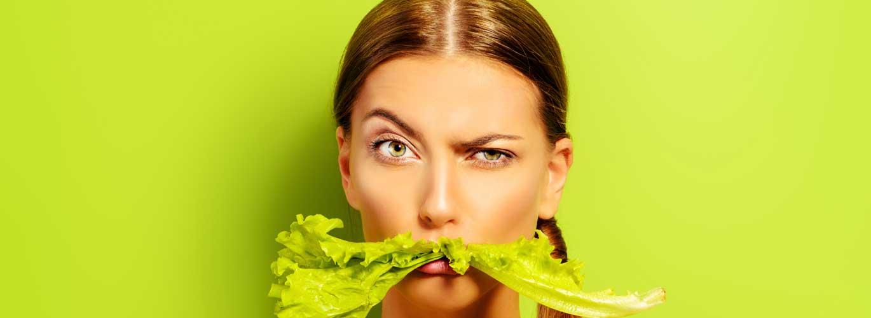 Diätassistent - Frau mit Salatblatt im Mund