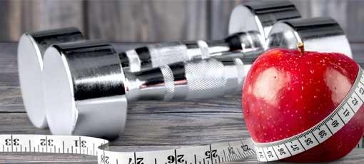 Apfel, Hanteln und Messband sind zu sehen