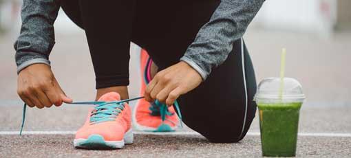 Sportlerin bindet sich die Schuhe - Smoothie steht auf dem Boden
