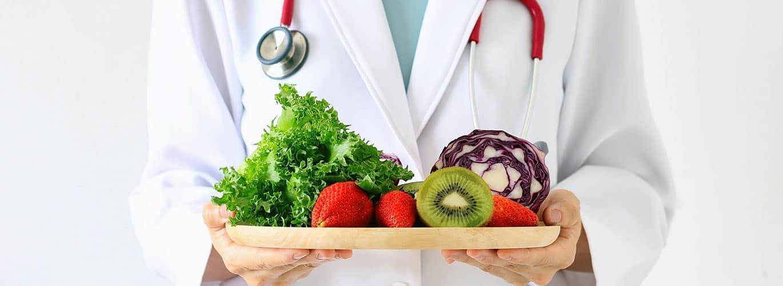 Ausbildung in der Ernährungsmedizin - Arzt hält Tablet mit Gemüse und Obst