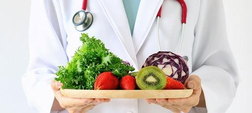 Arzt mit Gemüse und Obstteller