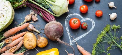 Tomaten liegen im Herz aus Kreide und Gemüse darum