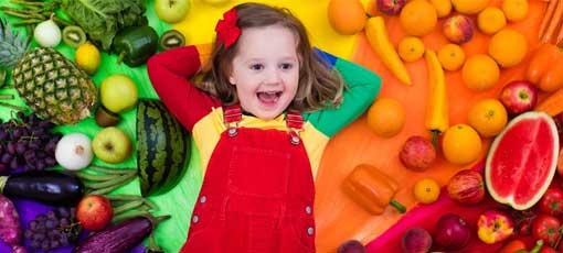 Bunt angezogenes Kind liegt zwischen Obst und Gemüse